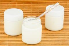Drie kruiken met huisyoghurt op een stromat Royalty-vrije Stock Fotografie