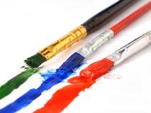 Drie kunstenaarsborstels met kleurrijke verf Royalty-vrije Stock Fotografie