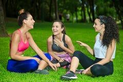 Drie lachende sportvrouwen op gras met gekruiste benen Royalty-vrije Stock Afbeelding