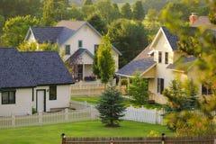 Drie landelijke huizen met witte piketomheiningen. Stock Afbeelding