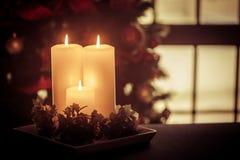Drie lange Kerstmiskaarsen tegen ruit stock fotografie