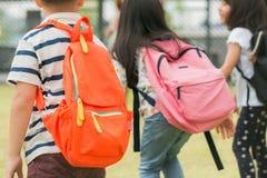 Drie leerlingen van lage school gaan hand in hand Jongen en meisje met schooltassen achter de rug Begin van schoollessen royalty-vrije stock foto
