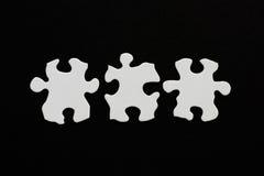 Drie lege gealigneerde raadselstukken losgemaakt op zwarte achtergrond Stock Foto's