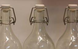 Drie lege glasflessen die zich op een rij bevinden stock foto's