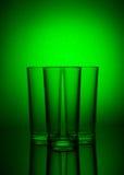 Drie lege glazen op groene achtergrond met bezinning Stock Foto's