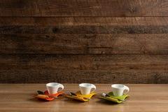 Drie lege koffiekoppen met koekje en theelepeltje dichtbij stock afbeelding