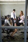 Drie leraren die in bibliotheekcomputerzaal samenkomen Stock Afbeeldingen