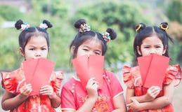 Drie leuke Aziatische kindmeisjes die rode envelop houden stock foto's