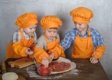 Drie leuke Europese jongens kleedden zich zoals de koks bezige kokende pizza zijn drie broers helpen mijn moeder om pizza te koke stock foto's