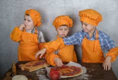 Drie leuke Europese jongens kleedden zich zoals de koks bezige kokende pizza zijn drie broers helpen mijn moeder om pizza te koke stock fotografie