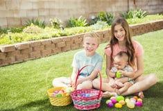 Drie leuke het glimlachen jonge geitjes die eieren op een Paaseijacht in openlucht verzamelen stock foto