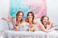 Drie leuke jonge meisjes sedyat op het bed in de ruimte, zijn holdin Stock Afbeeldingen