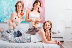 Drie leuke jonge meisjes sedyat op het bed in de ruimte, zijn holdin Royalty-vrije Stock Foto