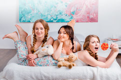 Drie leuke jonge meisjes sedyat op het bed in de ruimte, zijn holdin Stock Foto's