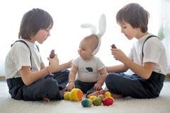 Drie leuke jongens, siblings die, broers, met paaseieren, e spelen stock fotografie