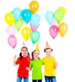 Drie leuke meisjes met gekleurde ballons Stock Foto's