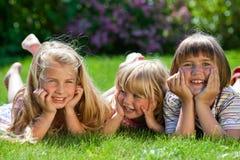 Drie leuke meisjes openlucht in gras het glimlachen Stock Foto's