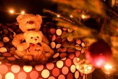 Drie leuke teddyberen door de Kerstboom Royalty-vrije Stock Afbeeldingen
