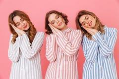 Drie leuke vrouwenjaren '20 die kleurrijke gestreepte pyjama's dragen die o slapen Royalty-vrije Stock Foto