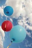 Drie levendige kleurenballons op blauwe hemel Stock Afbeelding