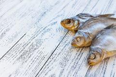Drie ligt de droge vissenbrasem op een lichte houten lijst stock foto