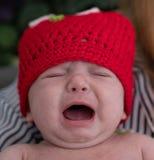 Drie-maand-oude baby met rode wolhoed stock fotografie