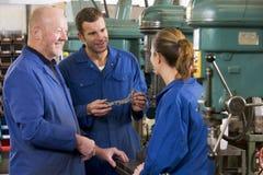 Drie machinisten in werkruimte door machine te spreken Stock Foto