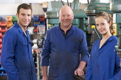 Drie machinisten in werkruimte door machine te spreken stock foto's