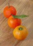 Drie mandarins op houten lijst, inbegrepen weg Royalty-vrije Stock Afbeeldingen