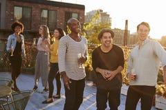 Drie mannelijke vrienden die en bij een dakpartij lachen drinken stock foto