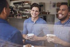 Drie mannelijke vrienden die over koffie bij een koffiewinkel lachen royalty-vrije stock afbeeldingen