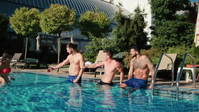 Drie mannen en de jonge vrouw in roze zwempak tonen duimen in de pool stock video