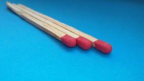 Drie matchsticks over blauwe achtergrond Close-up van matchsticks stock foto