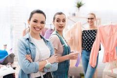 Drie meisjes bij kledingstukfabriek Één van hen houdt twee nieuwe kleding Glimlachende arbeiders stock foto's