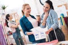 Drie meisjes bij kledingstukfabriek Zij bekijken blauwdrukken en het drinken koffie stock fotografie