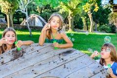 Drie meisjes die bellen in het park blazen Stock Fotografie