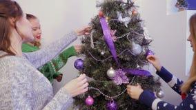 Drie meisjes die een Kerstboom en het spreken verfraaien stock video