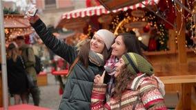 Drie Meisjes die een Selfie met Slimme Telefoon op de Kerstmismarkt nemen Gelukkige Vrouwen die Pret in openlucht op Kerstmis heb stock videobeelden