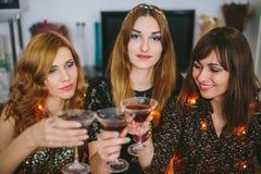 Drie meisjes die en Kerstmis of Nieuwjaar` s Vooravond drinken vieren Royalty-vrije Stock Foto