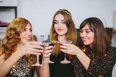 Drie meisjes die Kerstmis of Nieuwjaar` s Vooravond thuis vieren Stock Afbeeldingen