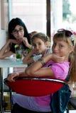Drie meisjes die in koffie zitten Stock Foto