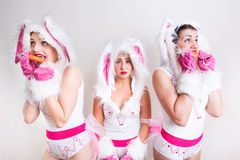 Drie meisjes die in konijnkostuum wortel eten Royalty-vrije Stock Foto's