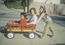Drie meisjes die met een rode wagen in Glendale, CA spelen stock foto