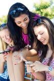 Drie meisjes die met hun smartphones babbelen Stock Foto