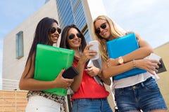 Drie meisjes die met hun smartphones bij de campus babbelen Stock Afbeeldingen