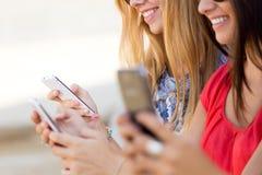 Drie meisjes die met hun smartphones bij de campus babbelen Royalty-vrije Stock Afbeeldingen