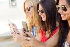 Drie meisjes die met hun smartphones bij de campus babbelen Stock Foto