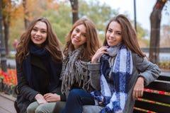 Drie meisjes die op de bank in openlucht zitten Royalty-vrije Stock Afbeelding