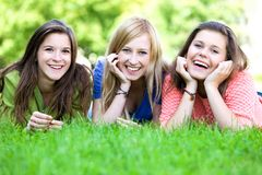 Drie meisjes die op het gras liggen Stock Fotografie