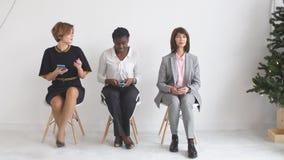 Drie meisjes die op stoelen zitten die op een baangesprek wachten stock footage